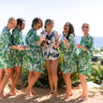 bridesmaids toast in robes by ocean